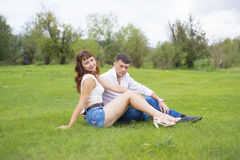 Lovers man and woman sitting on the green grass. Stock Image