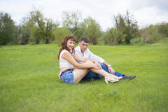 Lovers man and woman sitting on the green grass. Stock Images