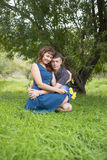 Lovers man and woman sitting in the shade of a leafy tree. Lovers men and women sitting in the shade of a leafy tree. A date in nature Stock Photo