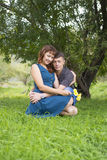 Lovers man and woman sitting in the shade of a leafy tree. Stock Photos