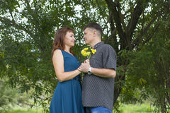 Lovers man and woman stand in the shade of a leafy tree. Royalty Free Stock Photography