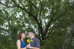 Lovers man and woman stand in the shade of a leafy tree. Lovers men and women stand in the shade of a leafy tree. A date in nature Stock Photo