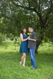 Lovers man and woman stand in the shade of a leafy tree. Royalty Free Stock Image