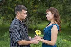 Lovers man and woman stand in the shade of a leafy tree. Royalty Free Stock Photo