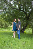 Lovers man and woman stand in the shade of a leafy tree. Stock Images