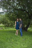 Lovers man and woman stand in the shade of a leafy tree. Royalty Free Stock Photos