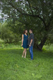 Lovers man and woman stand in the shade of a leafy tree. Stock Photography