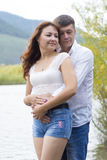 Lovers man and woman standing arm in arm by the river. Royalty Free Stock Photo
