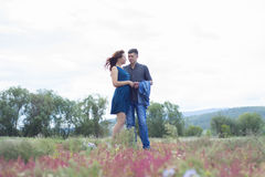 Lovers man and woman walk on field with red flowers. Royalty Free Stock Images