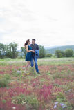 Lovers man and woman walk on field with red flowers. Royalty Free Stock Photography