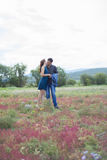 Lovers man and woman walk on field with red flowers. Royalty Free Stock Photos