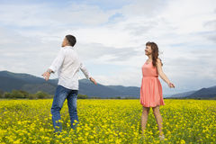 Lovers man and woman walk on the flower field. Lovers men and women walk on the flower field. A romantic date Royalty Free Stock Photography