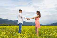 Lovers man and woman walk on the flower field. Lovers men and women walk on the flower field. A romantic date Royalty Free Stock Images