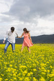 Lovers man and woman walk on the flower field. Lovers men and women walk on the flower field. A romantic date Royalty Free Stock Photos