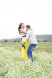 Lovers man and woman walk on the flower field. Lovers men and women walk on the flower field. A romantic date Stock Images