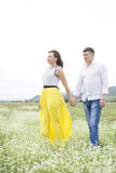 Lovers man and woman walk on the flower field. Lovers men and women walk on the flower field. A romantic date Royalty Free Stock Photo