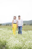 Lovers man and woman walk on the flower field. Lovers men and women walk on the flower field. A romantic date Royalty Free Stock Image