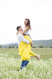 Lovers man and woman walk on the flower field. Lovers men and women walk on the flower field. A romantic date Stock Photography