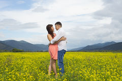Lovers man and woman walk on the flower field. Lovers men and women walk on the flower field. A romantic date Stock Photo