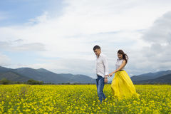 Lovers man and woman walk on the flower field. Royalty Free Stock Photography