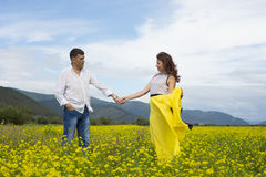 Lovers man and woman walk on the flower field. Royalty Free Stock Photos