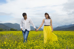 Lovers man and woman walk on the flower field. Royalty Free Stock Images