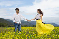Lovers man and woman walk on the flower field. Royalty Free Stock Image