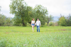 Lovers man and woman walking on green field. Royalty Free Stock Photos