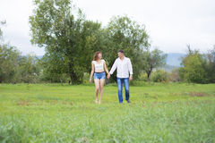 Lovers man and woman walking on green field. Stock Images