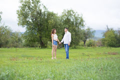 Lovers man and woman walking on green field. Stock Photography