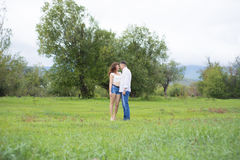 Lovers man and woman walking on green field. Stock Image