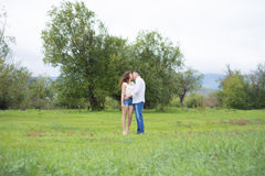 Lovers man and woman walking on green field. Stock Photos