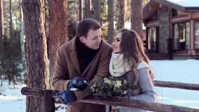 Lovers man and young woman walk near cottage with flowers in winter stock video footage