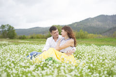 Lovers meet men and women on a beautiful flower field. Lovers men and women on a beautiful flower field. A romantic date Stock Image