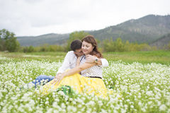 Lovers meet men and women on a beautiful flower field. Lovers men and women on a beautiful flower field. A romantic date Stock Photos