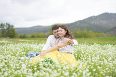 Lovers meet men and women on a beautiful flower field. Lovers men and women on a beautiful flower field. A romantic date Stock Photography