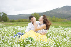 Lovers meet men and women on a beautiful flower field. Lovers men and women on a beautiful flower field. A romantic date Stock Images