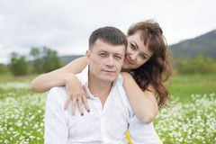 Lovers meet men and women on a beautiful flower field. Lovers men and women on a beautiful flower field. A romantic date Royalty Free Stock Photos