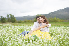 Lovers meet men and women on a beautiful flower field. Lovers men and women on a beautiful flower field. A romantic date Royalty Free Stock Images