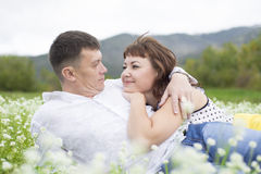 Lovers meet men and women on a beautiful flower field. Royalty Free Stock Photos