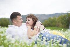 Lovers meet men and women on a beautiful flower field. Stock Photos