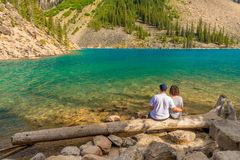 Lovers at Moraine Lake. Lovers sitting on a log at Moraine Lake, Banff National Park, Alberta Canada Royalty Free Stock Photography