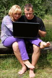 Lovers, nature and computer addiction Stock Photography