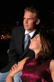 Lovers at Night. Two young lovers embrace at night with the city lights behind them Stock Image