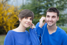 Lovers in the park listening to music with headphones Royalty Free Stock Photos