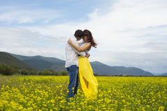 The lovers passionately embrace each other. The lovers passionately embrace each other on the flowery meadow Royalty Free Stock Photography