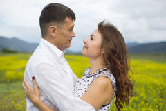 The lovers passionately embrace each other. The lovers passionately embrace each other on the flowery meadow Stock Photo