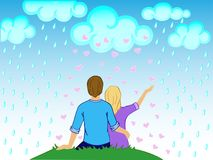 Lovers in the rain from the hearts. The girl and the boy are hugging. St. Valentine`s Day. A loving couple hugs sitting on a hill in the rain out of the hearts Stock Photos
