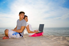 Lovers relaxing on the beach. Lovers relaxing by the beach with laptop on a beautiful day Royalty Free Stock Image
