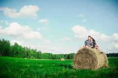 Lovers resting in a field near haystacks Stock Images